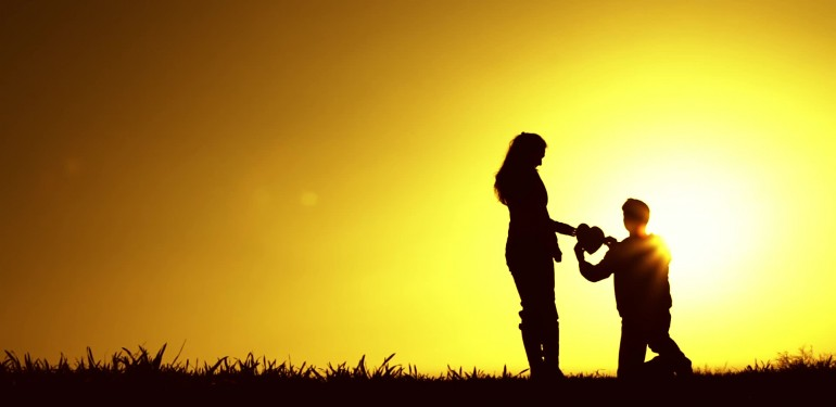 stock-footage-man-kneeling-giving-heart-proposal-love-sunset